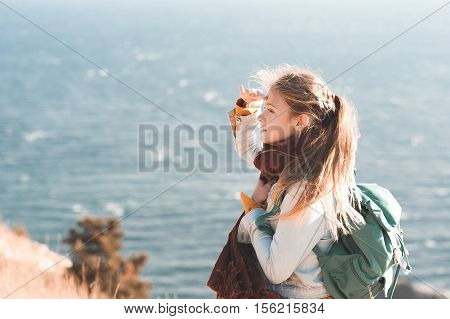 Teen girl traveler 14-16 year old looking ahead into distance. Wearing casual clothes and backpack outdoors over sea background.