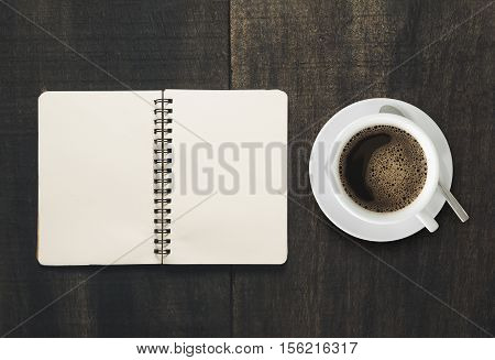 Open notebook with cup of coffee on black wooden desk. page Empty ready for your product display or montage.