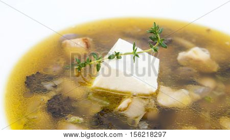 Soup with beans and mushrooms garnished with goat cheese
