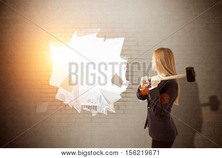 Woman is smashing wall with sledgehammer. Large city panorama is seen in the distancel. Concept of finding your way in business. Toned image