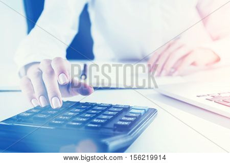 Close up of woman's hand on calculator's keyboard. Concept of accountant's work. Toned image