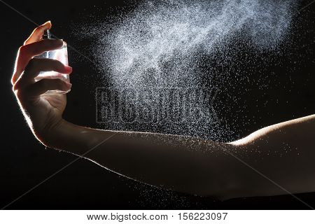 Hand spray perfume to body against black background