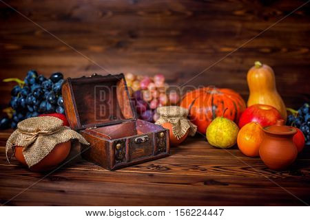 Thanksgiving Holiday Background With Opened Chest Treasure, Apple, Pear, Tomato, Grapes, Pot And Pum