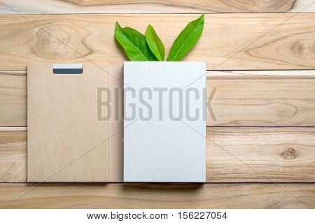 Recycled Paper Book Packaging with Green leaf on wood table for recycled paper construction products.Empty ready for your product display or montage.
