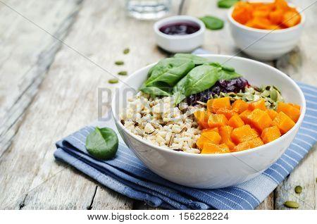 rice bowl with spinach pumpkin pumpkin seeds and cranberry sauce.