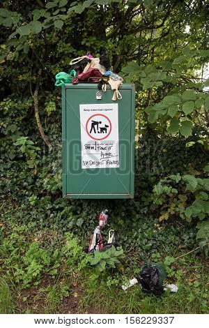 Overflowing bin filled with plastic bags of Dog poo