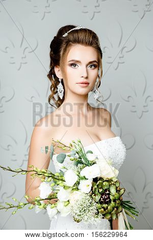 gorgeous bride in luxury wedding dress. Bride. Perfect Make up. Hairstyle, wedding jewelry. Beautiful Woman with Shiny Brown Hair. gorgeous wedding bouquet of various flowers.