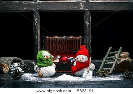 Handmade toy snowman and snowgirl of yarn skeins brooming and shoveling the snow over black background. Color toning