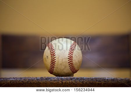 A well used and worn professional sized baseball sitting on wooden board
