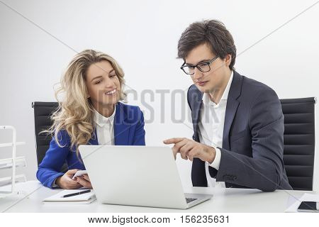 Guy Wearing Glasses Is Pointing At Computer Screen With His Colleague