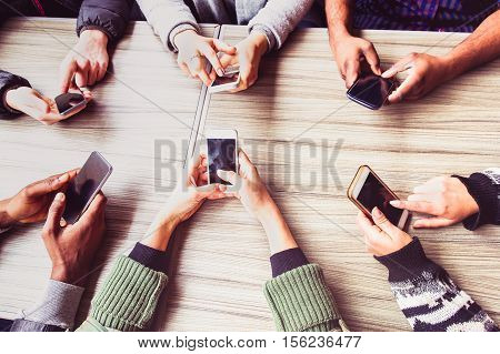 Group of friends having fun together with smart phones - Hands social networking with mobile device - Technology and phone addiction concept - Main focus on left bottom phone - Warm pink filter