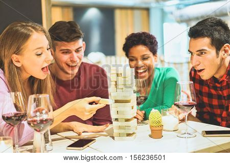 Group of young friends having fun playing board game in pub wine shop - Multiracial cheerful people smiling and enjoying time together indoor - Friendship concept - Focus on left girl eye