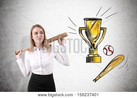 Front view of blond woman with baseball bat who is standing near concrete wall. Concept of changing business career for professional baseball one.