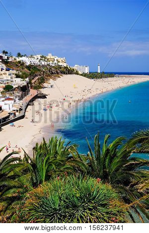 View from above on the beach Playa de Morro Jable with lighthouse on the Canay Island Fuerteventura Spain.