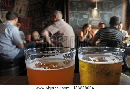 Two glasses of beer on a pub table with blurry figure of people drinking alcohol in the background