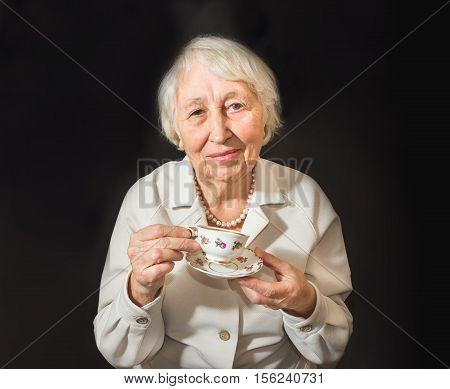 The Senior Woman Enjoying Cup Of Tea on black