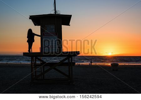 girl on a lifeguard tower in Newport Beach at sunset California
