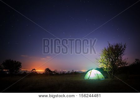 Tourist tent stands on glade under starry night sky and shines from within with city lights glow at the horizon.