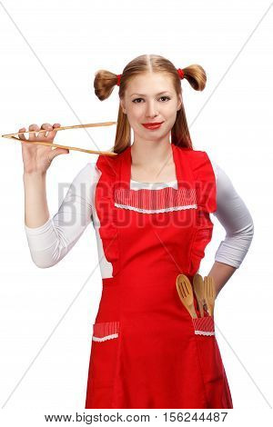 Young beautiful attractive smiling housewife in bright red apron with funny ponytails holding wooden salad tongs with wooden spoons and fork in pocket isolated on white background.