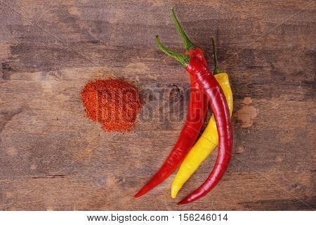 chili pepers an heap of powered peper over wooden background