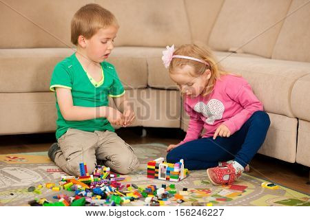 young children playing with blocks in livingroom