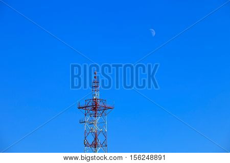 The moon and the TV tower are located on a clear blue sky day. Two single object. Abstract landscape. Clear sky. A natural phenomenon. Moon in the sky during the day. Industrial architectural object. TV tower, steel structure. The confrontation of the urb