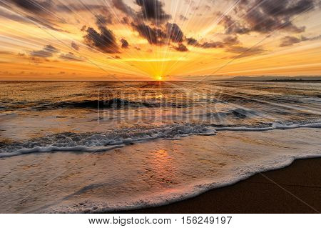 Ocean sunset rays is a brightburst of sun beams on the ocean horizon and a gentle wave rolling towards the beach.