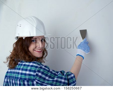 Smiling young woman in casual clothes in front of white unpainted wall in white helmet working with putty knife, happy people and construction concept