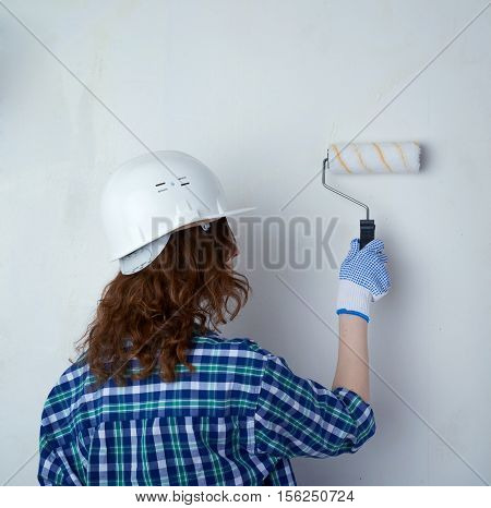 Young woman in casual clothes in front of white unpainted wall in white helmet working with paint roller, happy people and construction concept