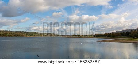 Panorama of Blagdon Lake, Somerset, UK. Resevoir at the edge of the Mendip Hills in England with flock of birds under blue sky with clouds