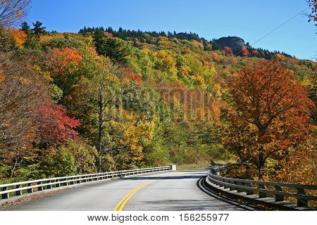 the Blue Ridge Parkway in North Carolina curves beneath a hillside covered in autumn foliage