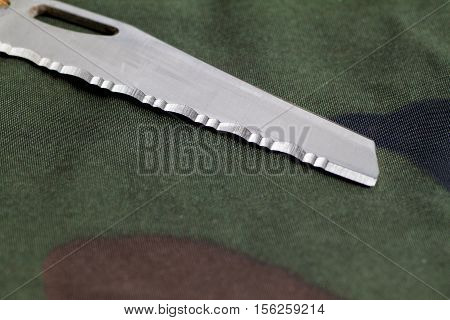 brilliant serreytornaya sharpening a knife blade on camouflage background