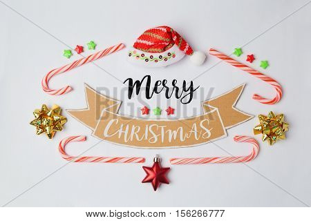 Merry Christmas banner with candy cane and Santa hat. View from above. Flat lay