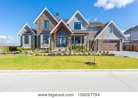 Custom built house on a sunny day with front yard and nicely trimmed lawn.