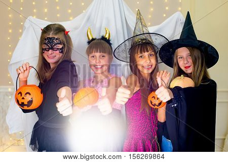 Group of teenagers wearing Halloween costumes fear of ghost near the table with pumpkins and bottle of potion at haloween party
