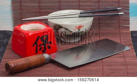 Chinese chef's cleaver knife cai dao on the table with brown mat