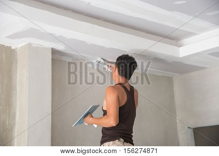 Worker working manual with wall plastering tools inside a house. Plasterer renovating indoor walls and ceilings with float and plaster,Worker painting the edges of the ceiling with Paintbrush