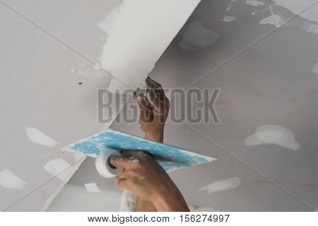 Worker working manual with wall plastering tools inside a house. Plasterer renovating indoor walls and ceilings with float and plaster,Worker painting the edges of the ceiling with Paintbrush poster
