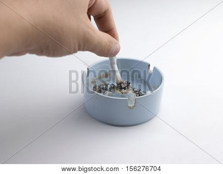 Hand Putting Out a Cigarette on a white background.