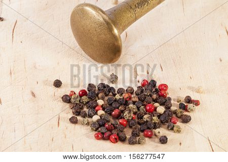 Grains of colorful pepper with mortal on wooden plank.