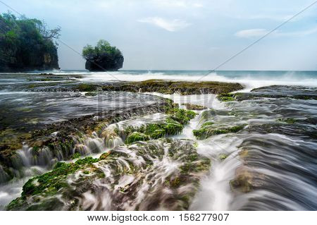 Seascape scenery of beautiful coral formation with sea water flow during mid day at Sawarna beach Banten Indonesia. Soft focus during long exposure shot.