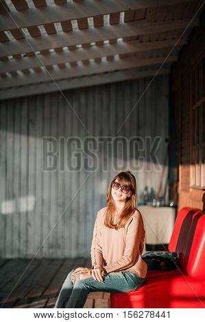 young modern girl on veranda. sunset evening in the village.