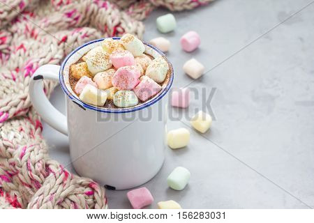 Homemade hot chocolate topped with marshmallow in enamel mug warm scarf on background horizontal copy space