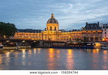 The French Institute and Pont des Arts across the Seine river at night Paris France