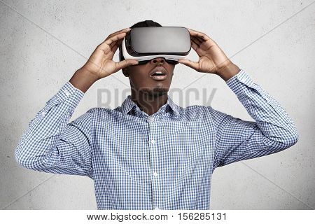 People technology innovation and gaming concept. Astonished African businessman in checkered shirt experiencing virtual reality while using oculus rift headset for entertaining himself in office