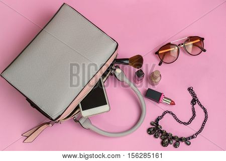 Woman handbag with makeup and accessories isolated on pink background