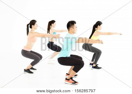 smiling young fit group stretching and squat