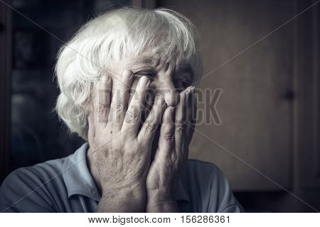 Sad elderly woman. She covered her face with her hands.