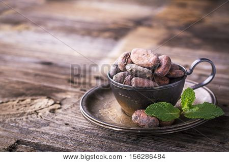 Cocoa beans are dried in vintage metal bowl on dark wooden background with a sprig of fresh mint. The concept of organic natural food. Hot winter drink for the whole family. selective focus