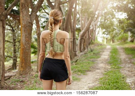 Rear View Of Young Woman Jogger With Fit Body Wearing Sports Bra And Black Shorts Standing Alone On